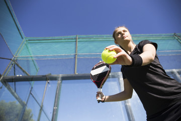 Low angle view of confident woman playing tennis in court against clear blue sky