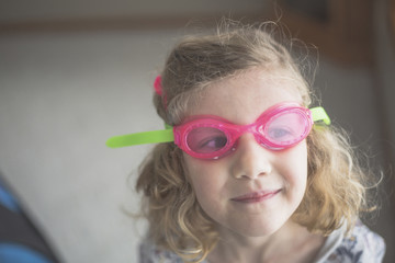 Close-up of girl in swimming goggles at home