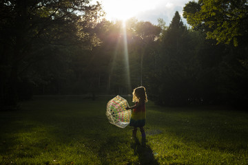 Girl playing with umbrella on grassy field in park
