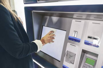 Midsection of woman scanning mobile phone while buying train ticket