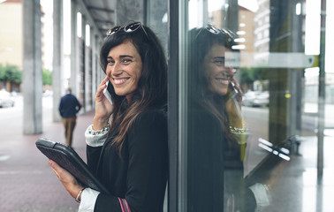 Portrait of happy woman talking on mobile phone while standing by window