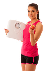 Woman holding scale and apple for healthy lifestyle and nutritio