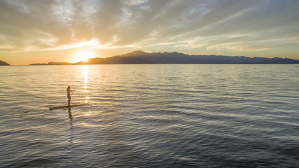 Woman paddleboarding in sea against cloudy sky during sunset