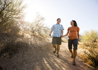 Happy couple walking on dirt road against clear sky