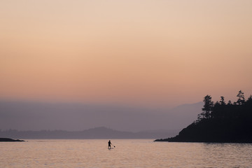 Silhouetted person paddleboarding in lake