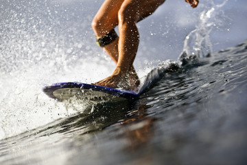 Low section of woman surfing in sea