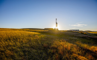 Oil pump on field against blue sky