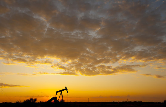 Silhouette oil pump on field against cloudy sky during sunset