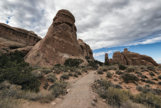 Rock formations by pathway against cloudy sky
