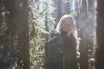 Portrait of woman hiking in forest during winter