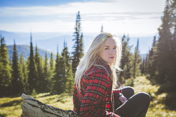 Portrait of woman sitting in forest on sunny day