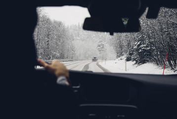 Cropped image of person driving car on snow covered road