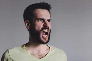 Young bearded man showing negative emotion, studio shot.