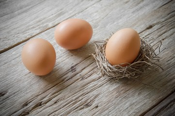 Chicken eggs on old wooden table background