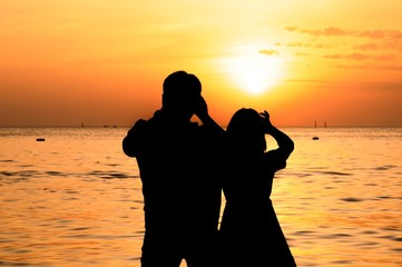 Silhouette of couple taking picture on the beach at sunset