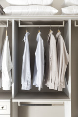 Clothes hang on a shelf in home closet