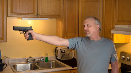 Man with handgun in kitchen with serious expression