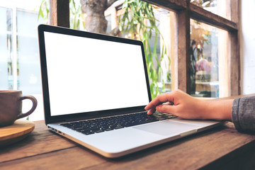 Mockup image of hand using laptop with blank white screen on vintage wooden table in cafe