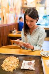 Woman taking photo on Okonomiyaki in Japanese restaurant