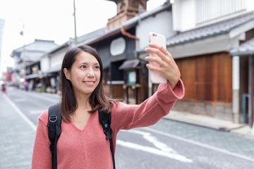 Woman taking selfie in Japanese street