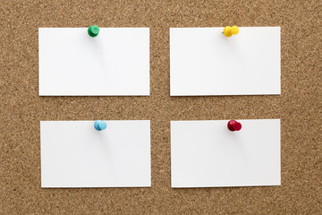 Four Blank Business Cards Pinned to Cork Board