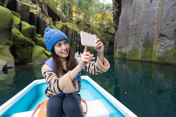Woman ftaking selfie and travel on boat in Takachiho gorge