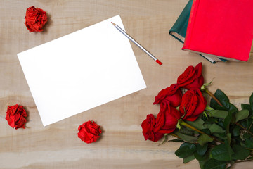 white sheet of paper lying on a wooden table with a bouquet of r