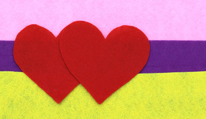 Close up of paper heart shapes on yellow, purple and pink backgr