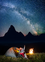 Night tent camping. Happy couple hikers sitting near tent and campfire and enjoying incredibly beautiful starry sky in the background silhouette of the mountains and luminous village in the valley