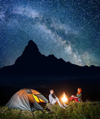 Night tent camping. Young couple hikers sitting near fire under incredibly beautiful starry sky and Milky way. In the background silhouette of the high mountains and luminous village in the valley