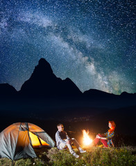 Night tent camping. Romantic pair hikers sitting near bonfire under incredibly beautiful starry sky and Milky way. In the background silhouette of the high mountains and luminous village in the valley