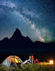 Romantic family hikers sitting by bonfire near lighting tent under incredibly beautiful starry sky. In the background silhouette of the mountains and luminous village in the valley at night. Low light