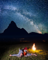 Twain lovers admiring incredibly beautiful starry sky and Milky way and lying near the bonfire at night. In the background silhouette of the mountains and luminous village in the valley