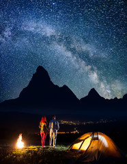 Happy tourist family - man and woman holding hands, standing near campfire and enjoying starry sky, silhouettes of the mountains and luminous village in the valley. Long exposure
