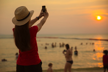 Girl relaxing beside sea beach with shot photo sunset by smart phone and blur tourist playing sea