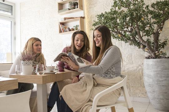 Three girls reading magazine on the cafe