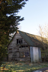 Old derelict empty wooden barn in country