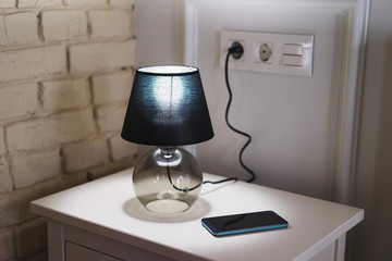 Coziness at home. Modern interior design. White bedside table with smartphone and black lamp on it. Minimalistic scandinavian composition. Comfortable life concept.