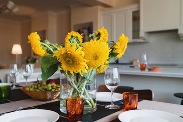Coziness at home. Modern interior design. Bouquet of sunflowers on the dining table.