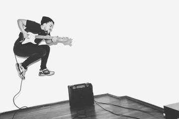 Awesome crazy fashion young musician rock guitar player jumps with passion in studio. Stylish rocky emotional man. Black and white toned.