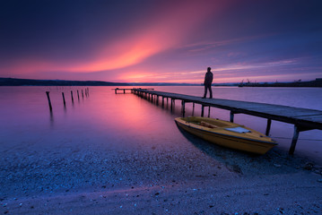 Sunset glow / Long time exposure view with boat in the lake and а silhouette of a man watching the sunset