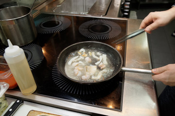 Chef is cooking fish in boiling stock