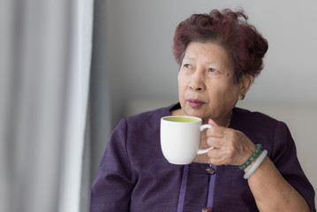 Asian senior woman drink a cup of tea near window with warm ligh
