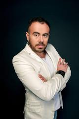 Portrait of man in white suits on dark background