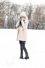 A young woman in a park full of snow