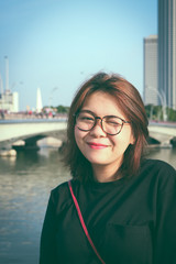 A beautiful Asian woman with glasses smiling with blur background in vintage style.