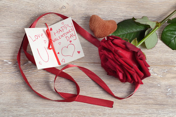 Valentine's day concept with toy heart, hand write love message and red rose on wooden background