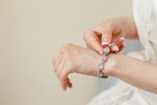 Bride's hands with simple manicure buttons bracelet
