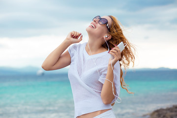 Portrait of a smiling young girl with earphones listening to music outdoors by the beach with ocean blue sky background