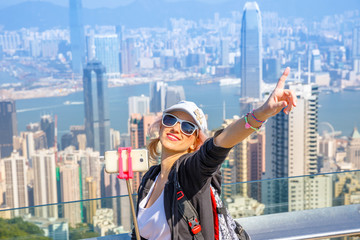 Traveler freedom asia concept. Hong Kong Victoria Peak tourist taking selfie stick picture photo with smartphone enjoying view over Victoria Harbour from Peak Tower. Defocused background.